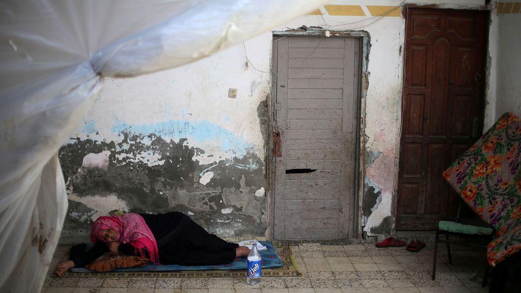 Una mujer palestina descansa en su vivienda en un campo de refugiados de la Franja de Gaza
