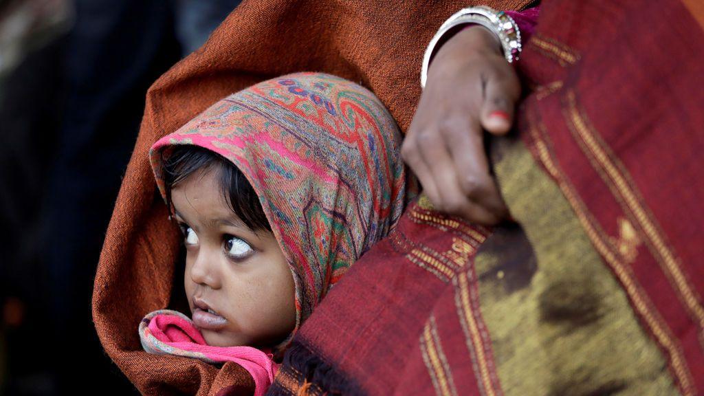 Una niña envuelta en un chal observa mientras espera junto con su madre un tren en la estación de ferrocarril en una fría mañana de invierno en Nueva Delhi, India