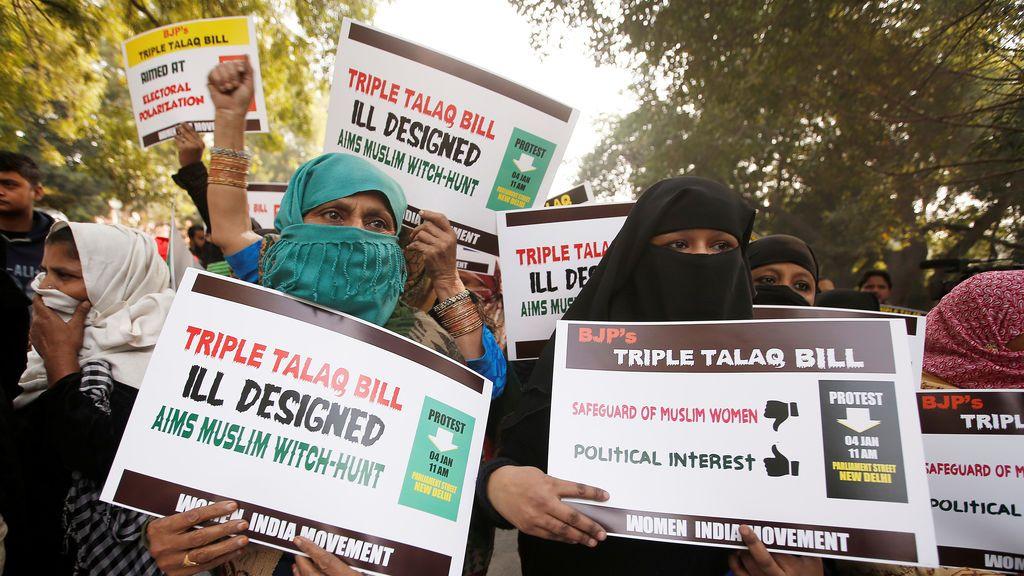 """Mujeres musulmanas sostienen pancartas durante una protesta contra un proyecto de ley aprobado la semana pasada por la cámara baja del Parlamento de India, que persigue perseguir a hombres musulmanes que se divorcian de sus esposas mediante el """"triple talaq"""" en Nueva Delhi, India"""