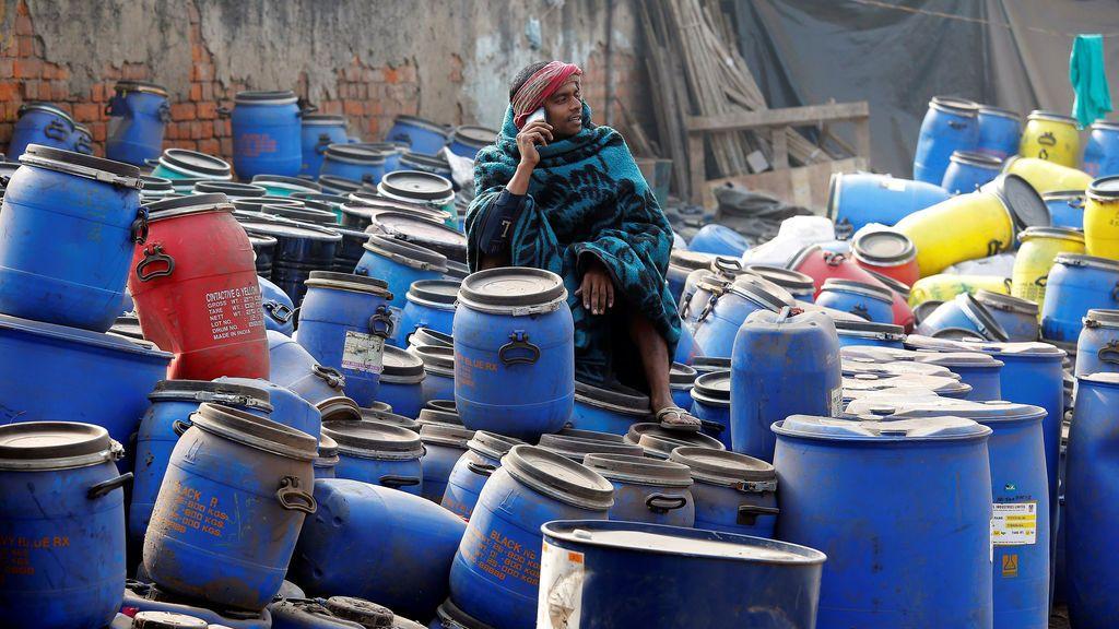 Un trabajador habla por teléfono mientras se sienta en contenedores de productos químicos cerca de un mercado mayorista en una mañana de invierno en Calcuta, India