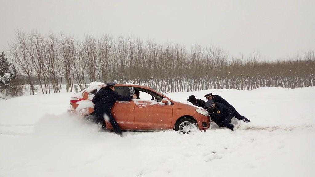 Los agentes del orden público ayudan a empujar un automóvil en la nieve en Xiangyang, provincia de Hubei, China
