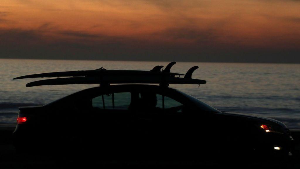 Un surfista deja la playa en su automóvil después del atardecer en Solana Beach, California, EE. UU.