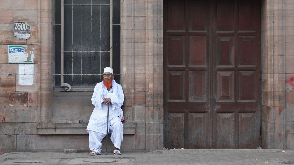 Un hombre con una barba teñida de henna se sienta frente a un edificio, construido en la época del Raj británico, mientras esperaba un autobús temprano en la mañana en Karachi, Pakistán