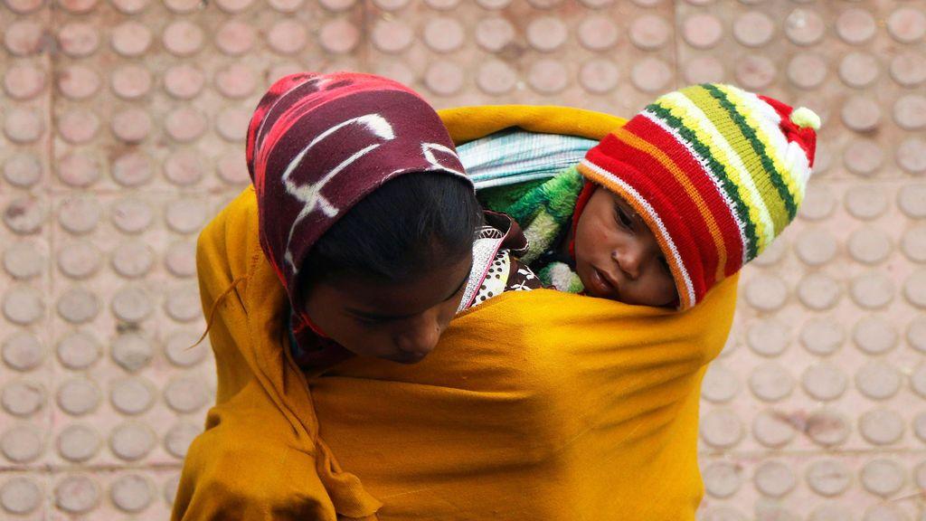 Una mujer envuelve a un niño en un chal mientras espera el tren en la estación de ferrocarril en una nebulosa mañana de invierno en las afueras de Agartala, India