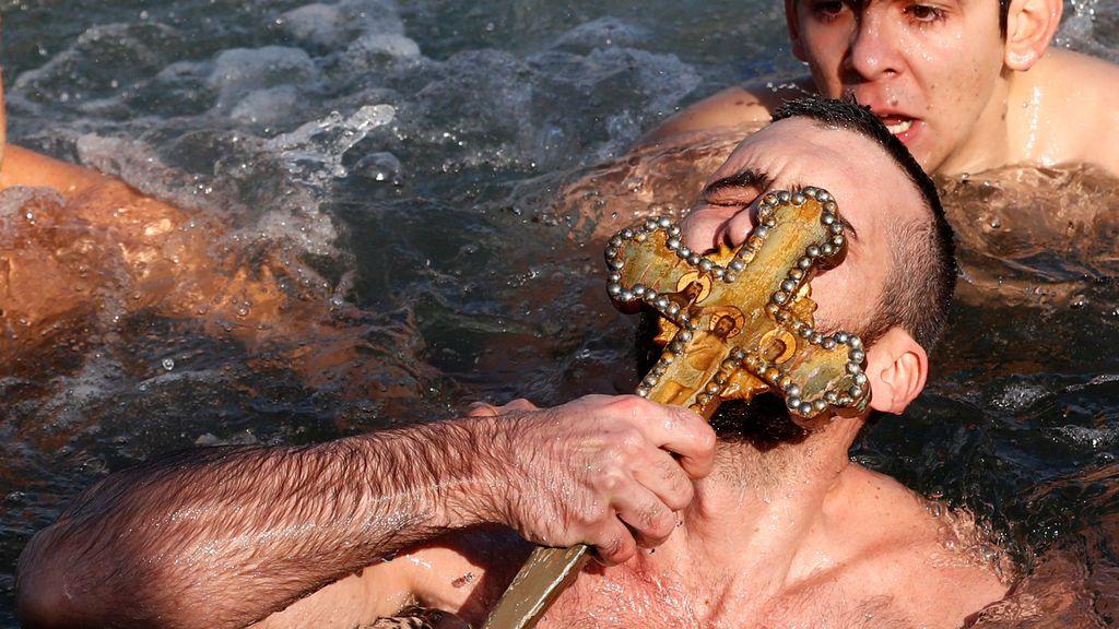 El fiel ortodoxo griego Nikolas Solís, un peregrino de Grecia, besa un crucifijo de madera mientras nada en el Cuerno de Oro en Estambul, Turquía