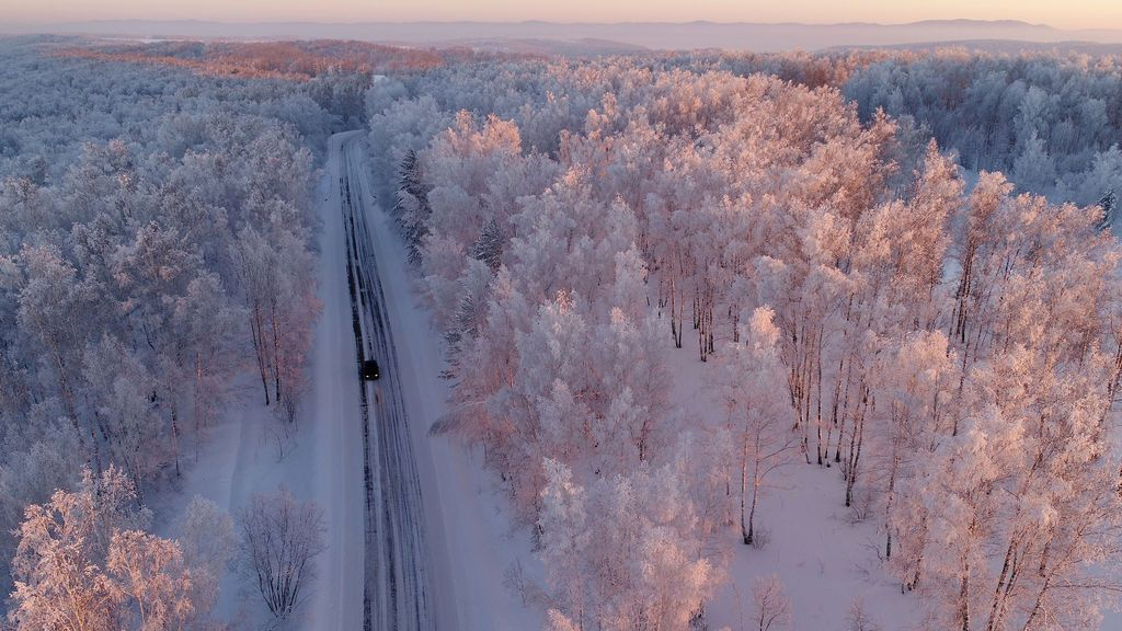Un automóvil conduce a lo largo de un camino forestal durante la puesta del sol, con una temperatura de -27ºC en la zona de Siberia Taiga en las afueras de Balakhta, en la región de Krasnoyarsk, Rusia