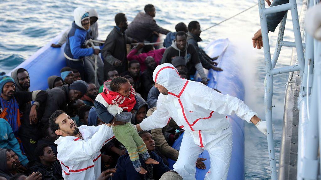Un niño migratorio es llevado mientras otros socorristas en un lúgubre son rescatados por guardias costeros libios frente a la costa de Garabulli, al este de Trípoli, Libia