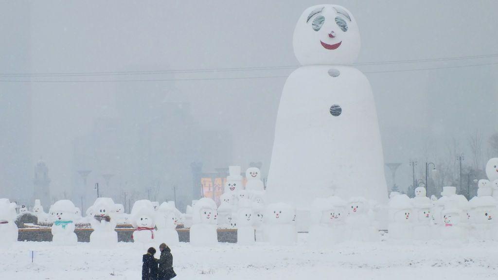 Las personas se ven junto a un muñeco de nieve gigante en un parque en Harbin, provincia de Heilongjiang, China