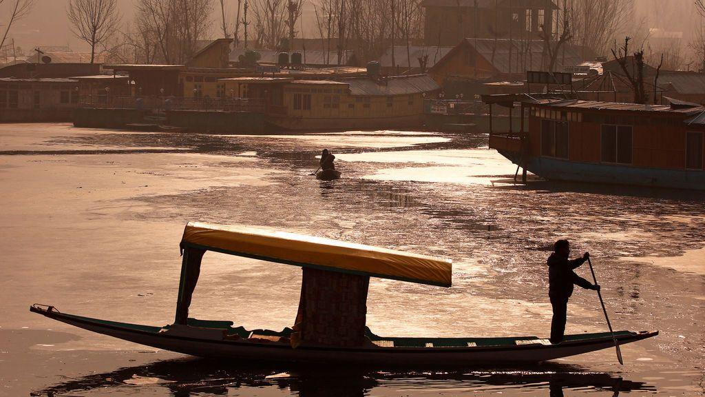 Un hombre sube su bote en interiores parcialmente congelados del lago Dal en una fría mañana de invierno en Srinagar