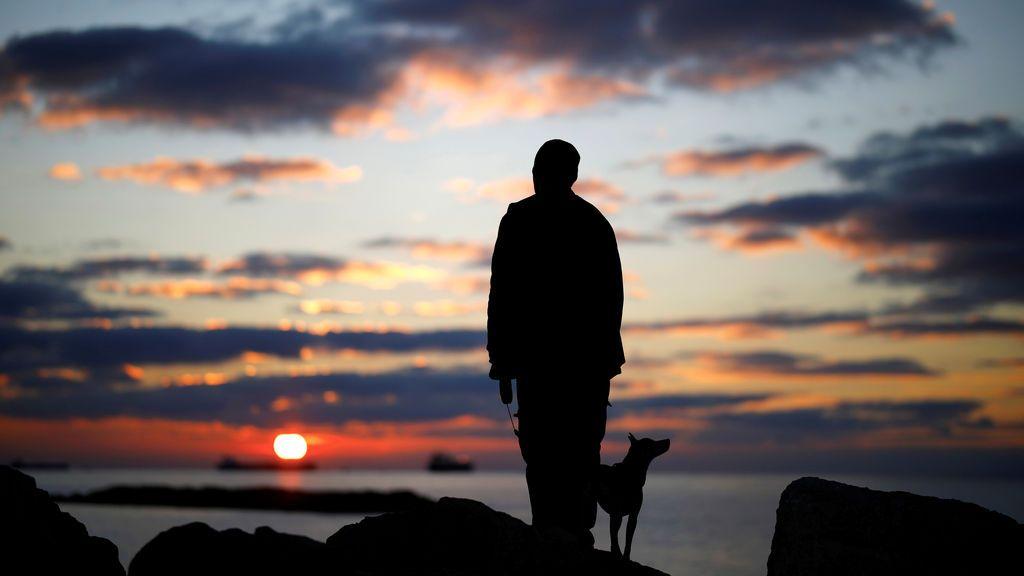 Un hombre observa el atardecer con su perro en un rompeolas, a lo largo de la orilla del mar Mediterráneo en Ashkelon, Israel