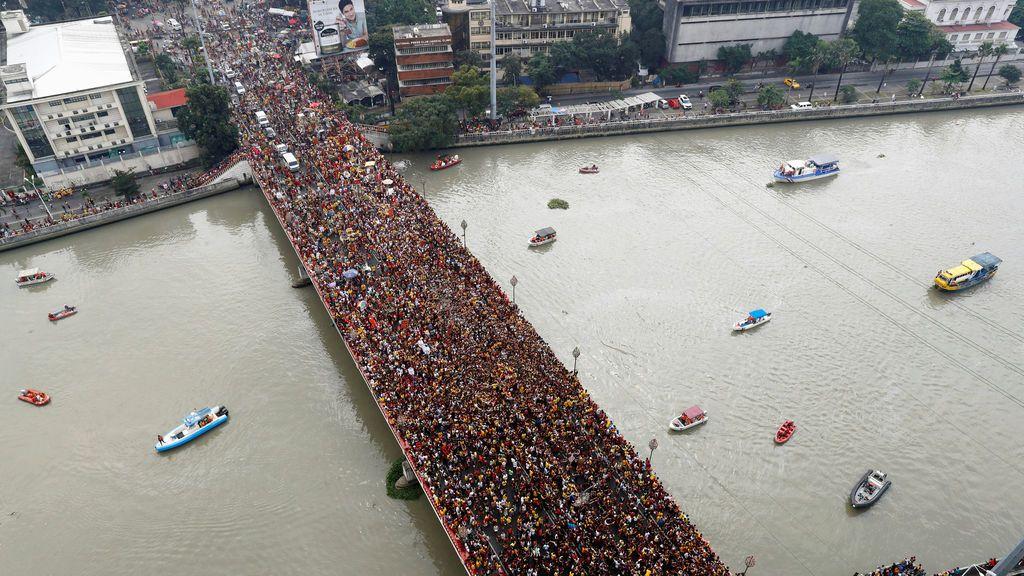 Los devotos acuden en masa mientras un carruaje con una imagen del Nazareno Negro se abre paso a través del puente Jones en Manila, Filipinas