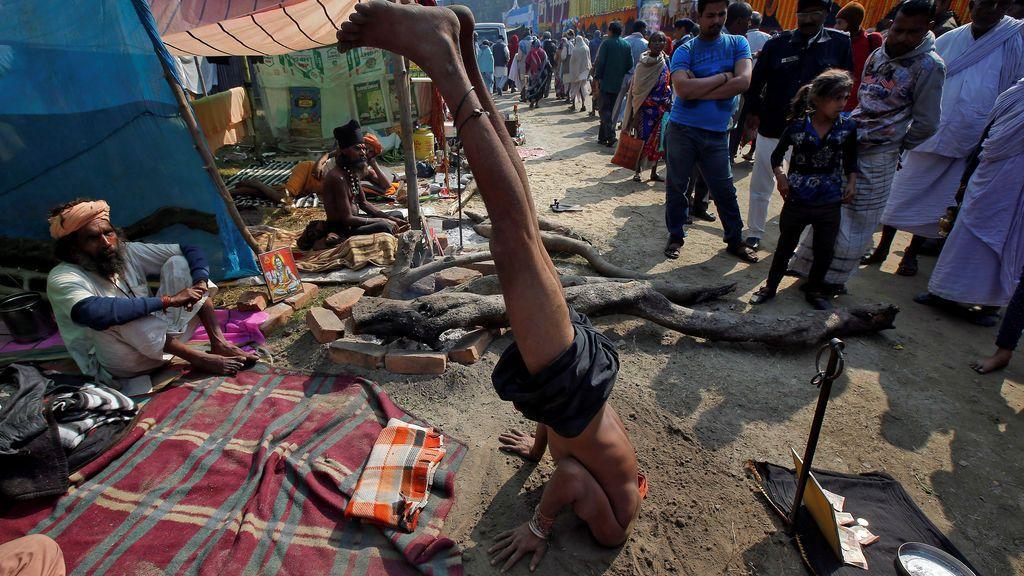 """Un Sadhu o un hombre santo hindú se sitúa de esta forma para recibir dinero de los peregrinos en un refugio improvisado, antes de dirigirse a un viaje anual a la isla Sagar para el festival de un día de """"Makar Sankranti"""", en Calcuta, India"""
