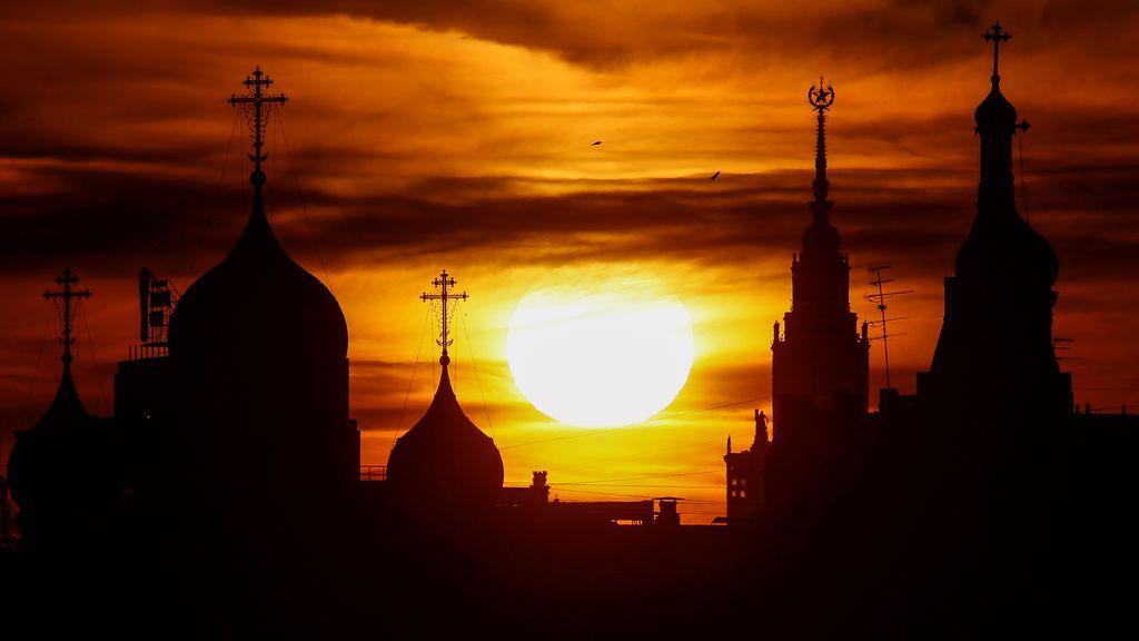El sol se pone sobre las cúpulas del Monasterio Andreevsky y del edificio principal de la universidad de Lomonosov Moscow, en Moscú, Rusia