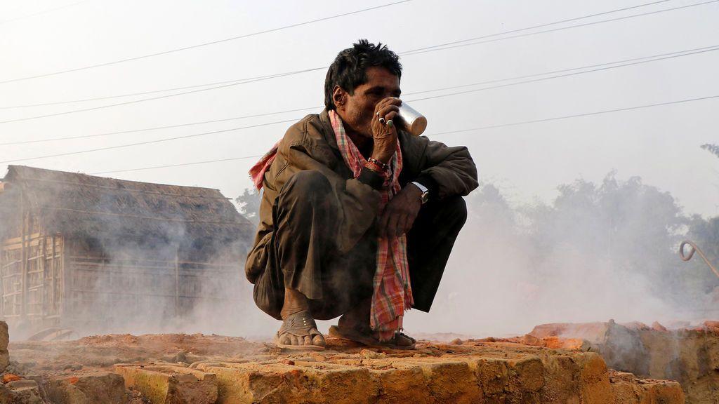 Un trabajador bebe té dentro de una fábrica de ladrillos en una fría mañana de invierno en las afueras de Agartala