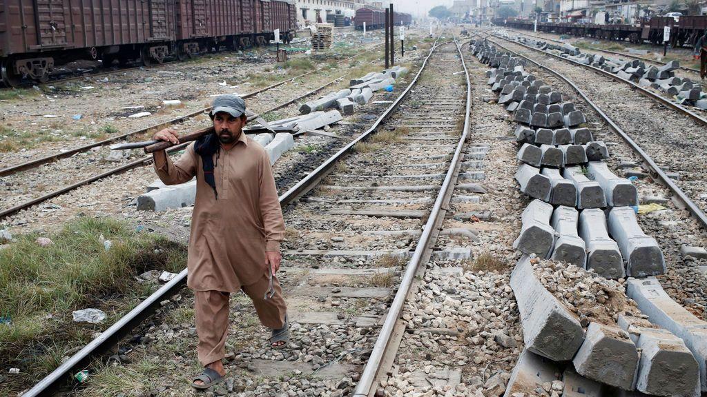 Un obrero camina con herramientas junto a las pilas de traviesas para ser reemplazadas a lo largo de las vías del tren en Karachi, Pakistán