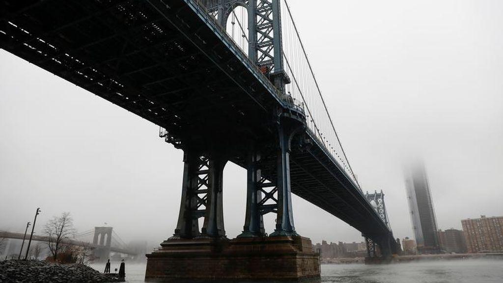 El cielo y los rascacielos de Manhattan cubiertos completamente por las nubes, fotografía tomada desde la parte de abajo del puente de Brooklyn