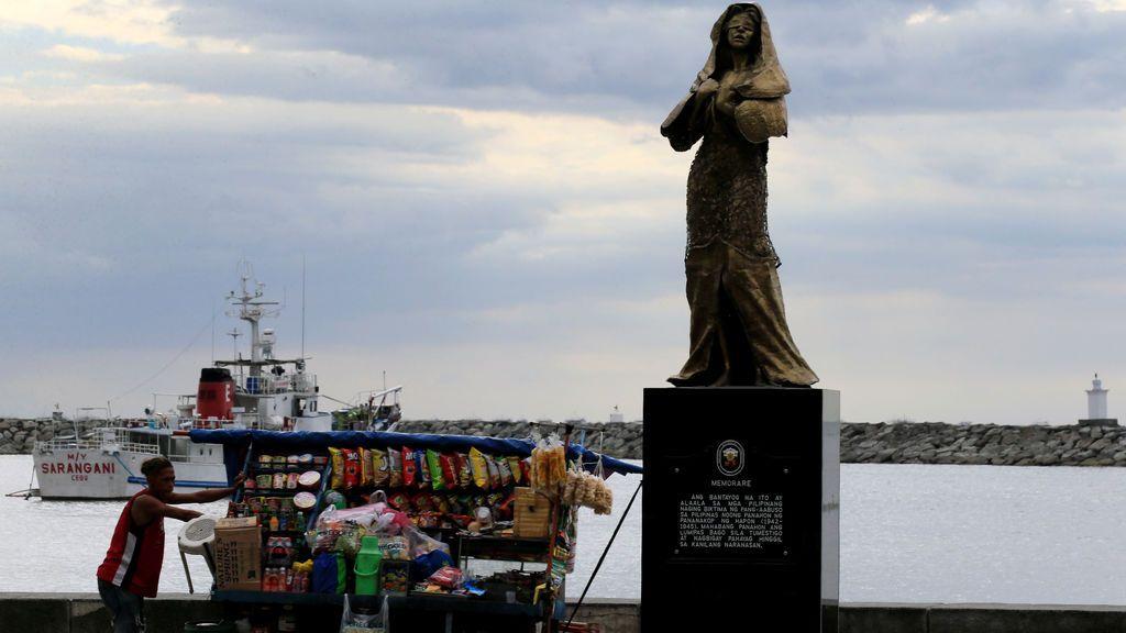 Un vendedor empuja un carro más allá de una estatua que conmemora a las mujeres filipinas que trabajaron en burdeles militares japoneses durante la Segunda Guerra Mundial