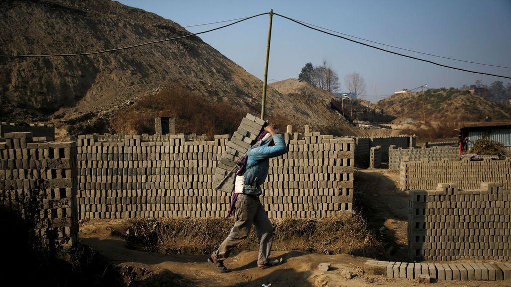 Un trabajador que lleva ladrillos en la espalda camina mientras trabaja en una fábrica de ladrillos en Bhaktapur, Nepal
