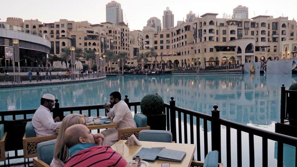 Comensales sentado en una terraza con vistas a un lago en un restaurante de Dubai, Emiratos Árabes