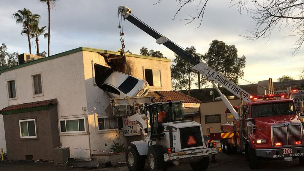 Los trabajadores de rescate retiran un automóvil que se estrelló contra un edificio después de saltarse una mediana y salir al aire, según los medios locales, en Santa Ana, California, EE. UU