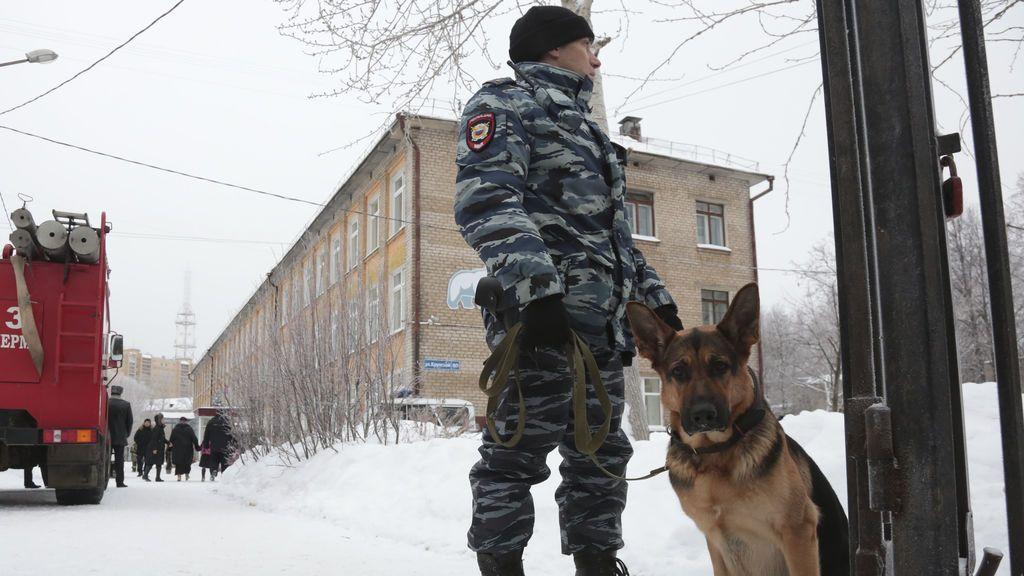 Un policía con un perro monta guardia cerca de una escuela local después de que supuestamente varias personas no identificadas con máscaras hiriesen a escolares con cuchillos en la ciudad de Perm, Rusia