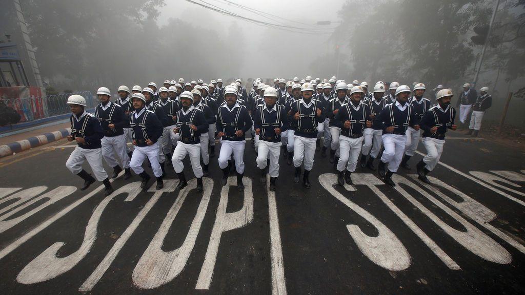 Los oficiales de la policía de tránsito se preparan antes de participar en un ensayo para el desfile del Día de la República en una mañana de invierno en Kolkata, India