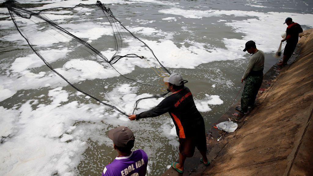 Grupo de hombres arroja su red en un río contaminado de Yakarta, Indonesia