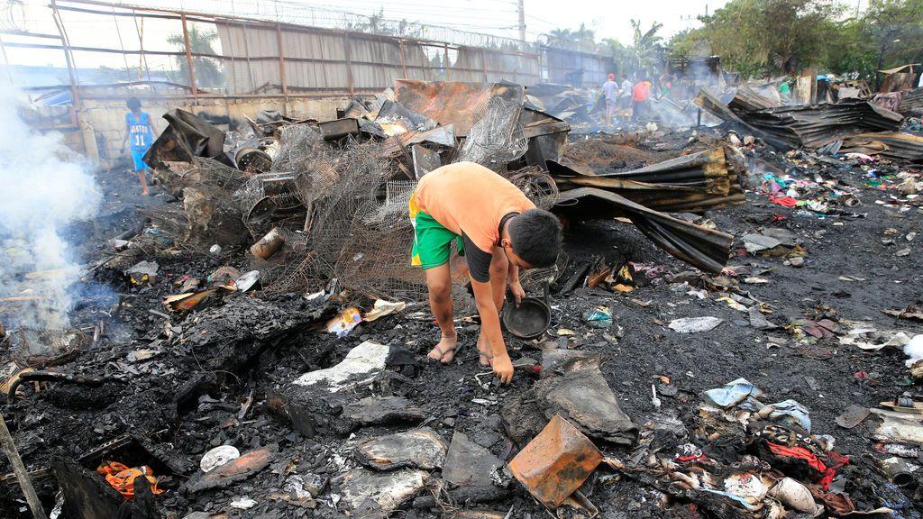 Un niño busca objetos después de un incendio que quemó varias casas y dejó a las familias sin hogar, en la ciudad de Bicutan, al sur de Manila, Filipinas