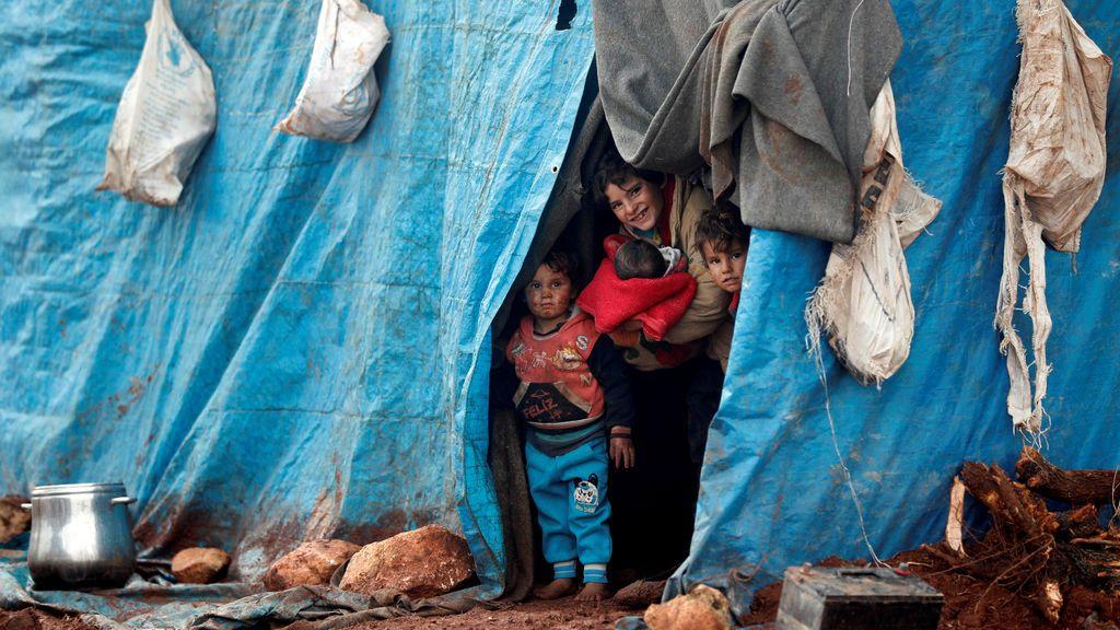 Niños sirios sonriendo desde la tienda que han fabricado en el campo de refugiados de Kelbit, cerca de la frontera entre Siria y Turquía