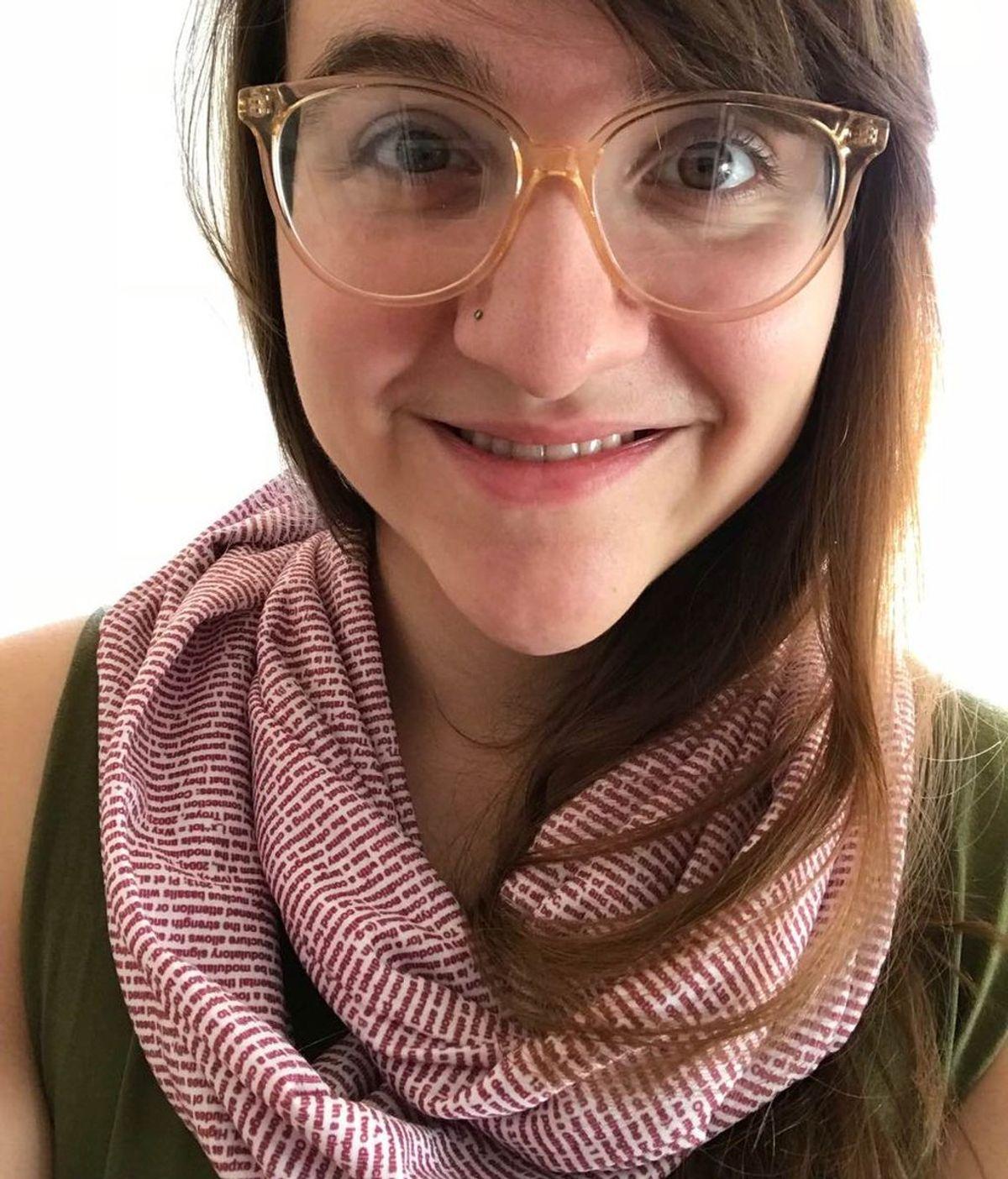 Una joven luce orgullosa su tesis…¡impresa en una bufanda!