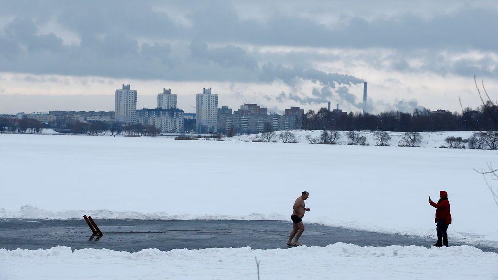 Un hombre corre tras bucear en las heladas aguas de un lago durante las celebraciones de la Epifanía Ortodoxa en Minsk, Bielorrusia