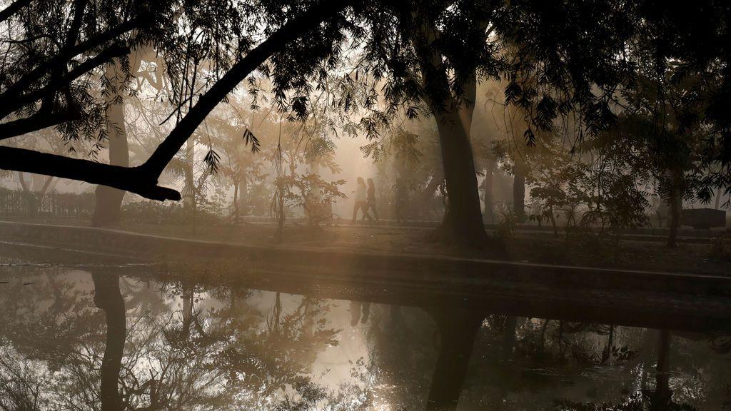 Gente caminando junto a un lago en un parque público en una mañana de invierno en Nueva Delhi, India