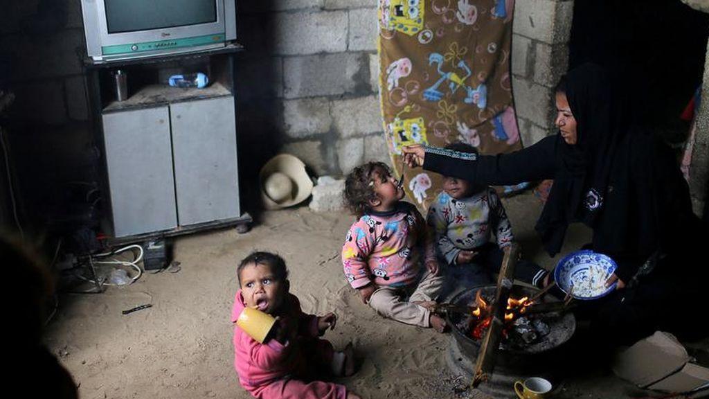 Una mujer palestina alimenta a sus hijos sentados junto a un fuego en un día lluvioso en Khan Younis en el sur de la Franja de Gaza