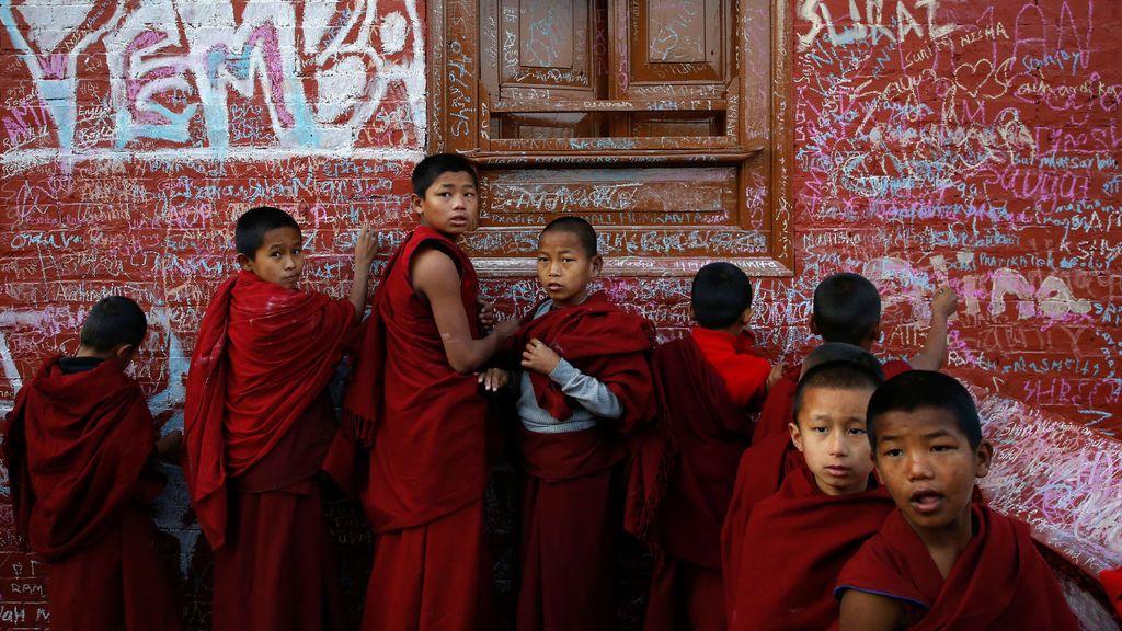 Jóvenes monjes escriben en la pared de un templo de Saraswati durante el festival Shreepanchami dedicado a la diosa de la educación Saraswati, en Katmandú, Nepal