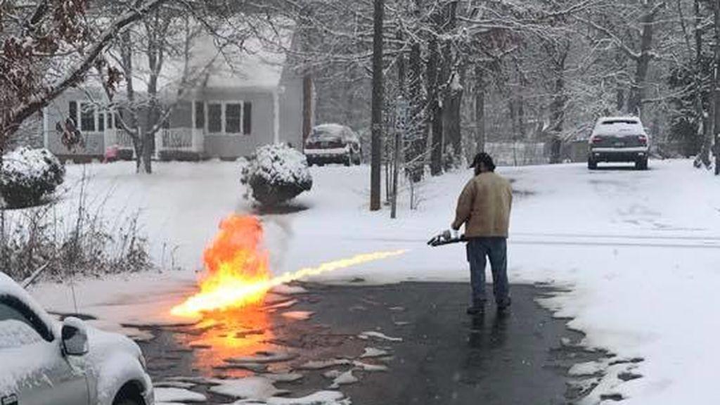 Un estadounidense usa un lanzallamas para quitar la nieve de la carretera