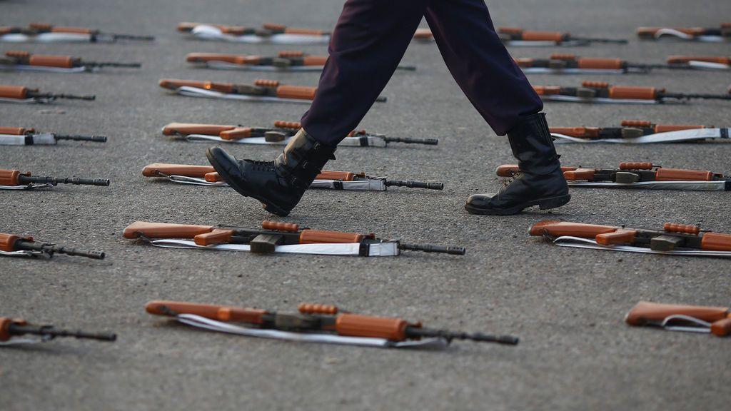 Un soldado indio pasa junto a los rifles durante un ensayo para el desfile del Día de la República en una mañana de invierno en Nueva Delhi, India