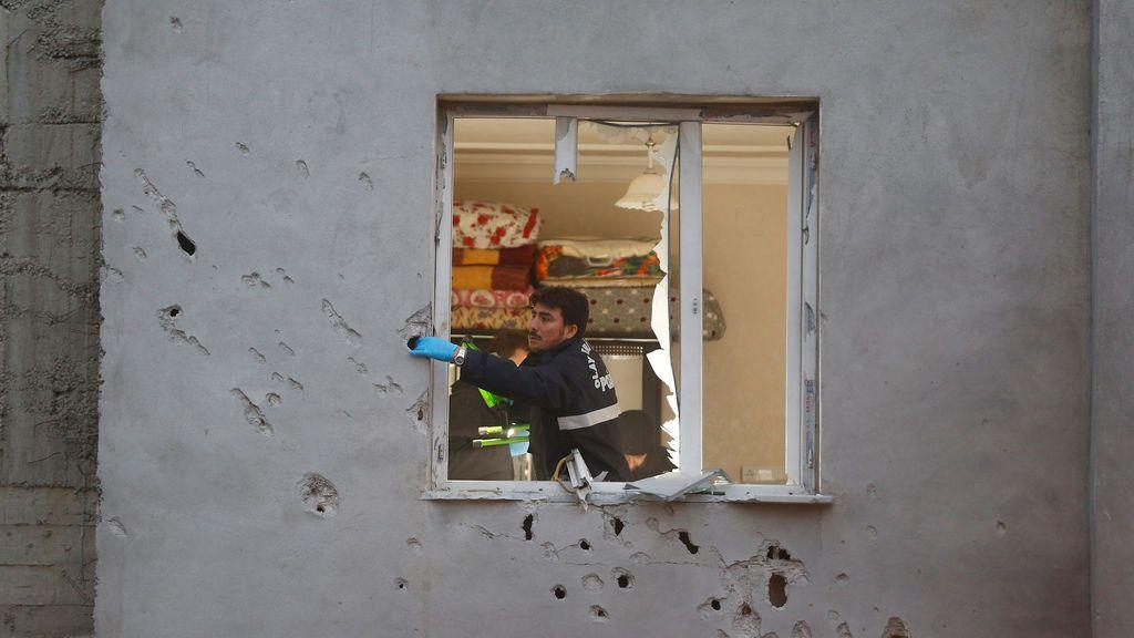 Los expertos forenses de la policía examinan un edificio que fue dañado después de que un cohete disparado desde Siria aterrizó cerca, en la ciudad fronteriza de Kilis, Turquía.