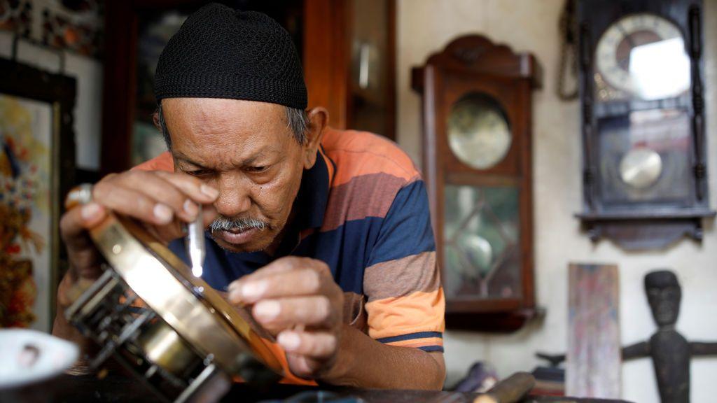 Un hombre arregla un reloj de pared en una tienda de un mercado de antigüedades en Yakarta, Indonesia