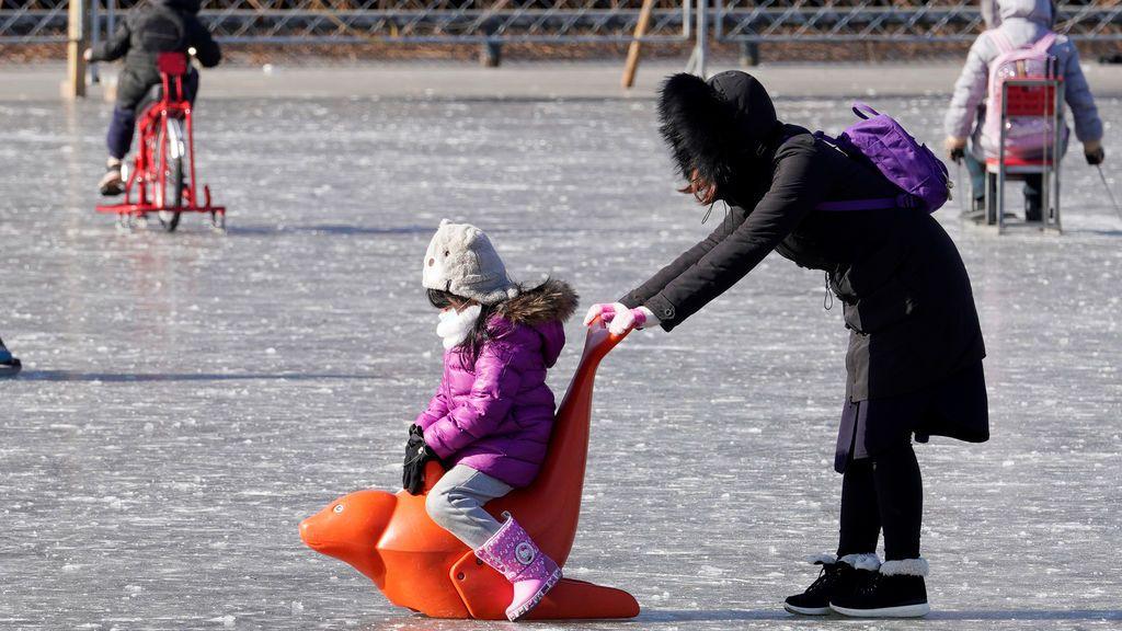 Una niña juega en el lago Houhai congelado en el centro de Beijing, China