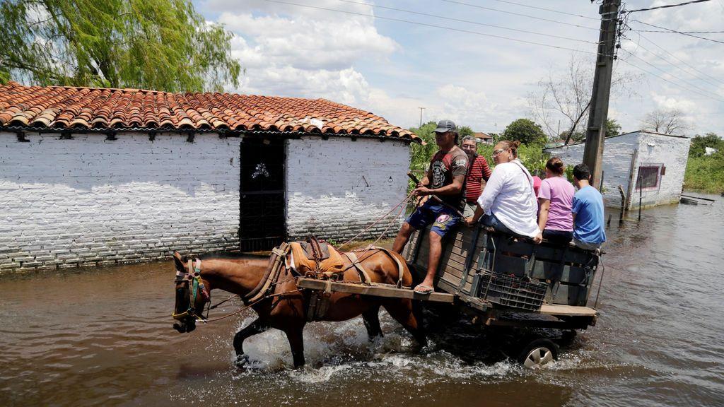La gente monta en un carruaje de caballos a través de una calle inundada después de que las fuertes lluvias hayan causado el desbordamiento del río Paraguay, en Asunción, Paraguay