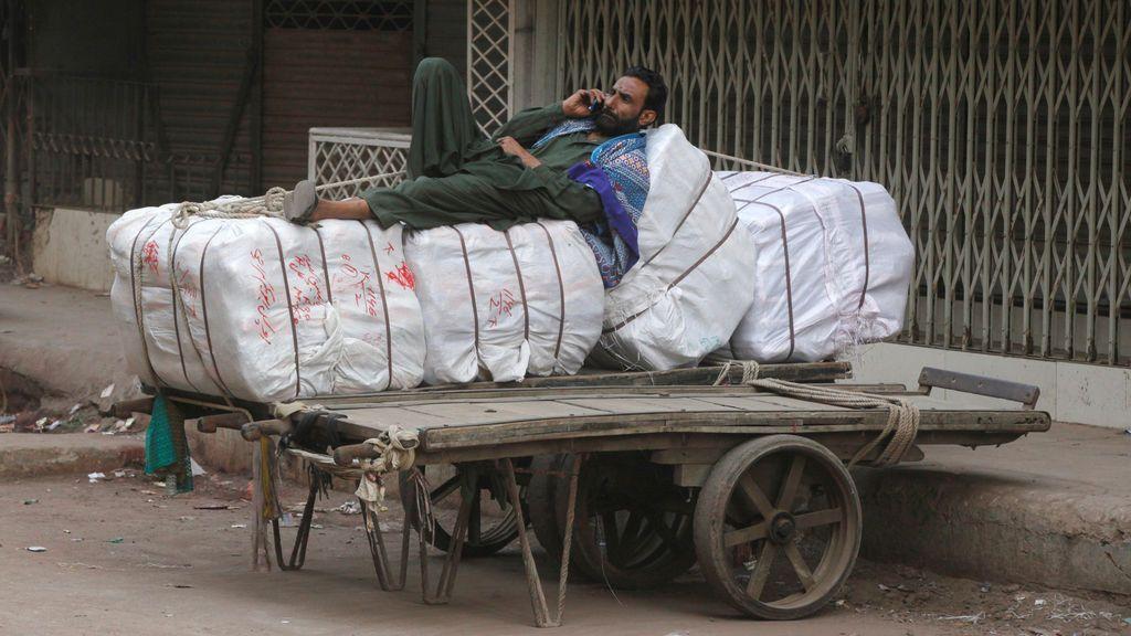 Un trabajador habla por el móvil mientras espera que se abra el mercado para entregar suministros a primera hora de la mañana en Karachi, Pakistán