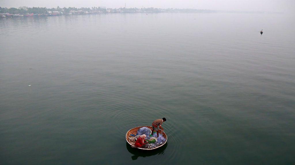 Un pescador y su esposa pescan en las aguas del lago Vembanad en Kochi, India