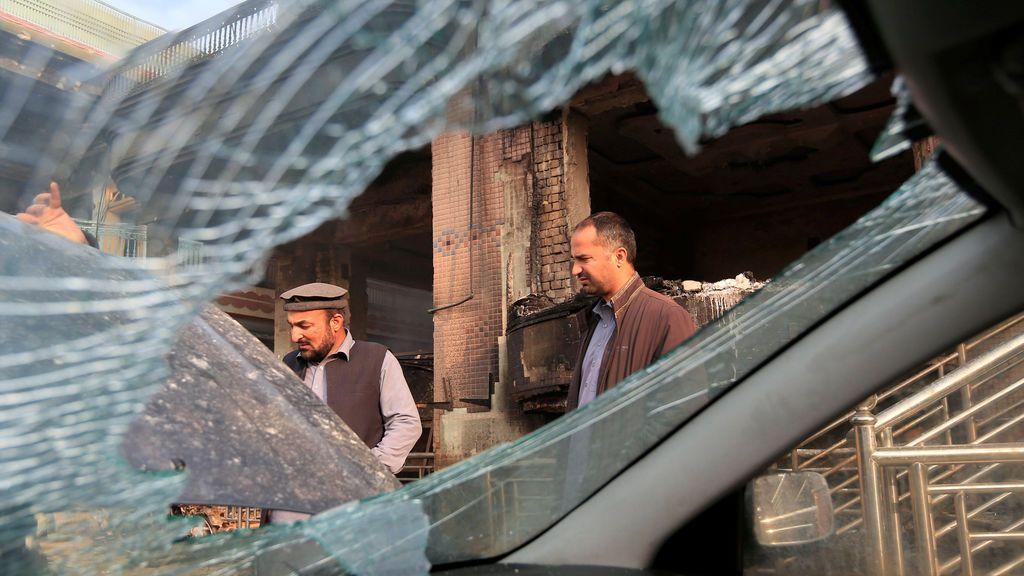 Dos hombres inspeccionan cómo han quedado los coches después de una explosión y varios disparos en Jalalabad, Afganistán