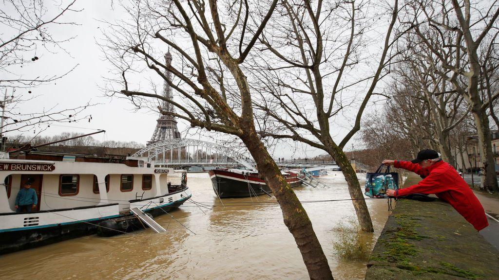 Un hombre usa una cuerda para transferir una bolsa con víveres a su amigo, que vive en una casa-barco debido al desbordamiento del río Sena tras varios días de intensas lluvias en París, Francia.
