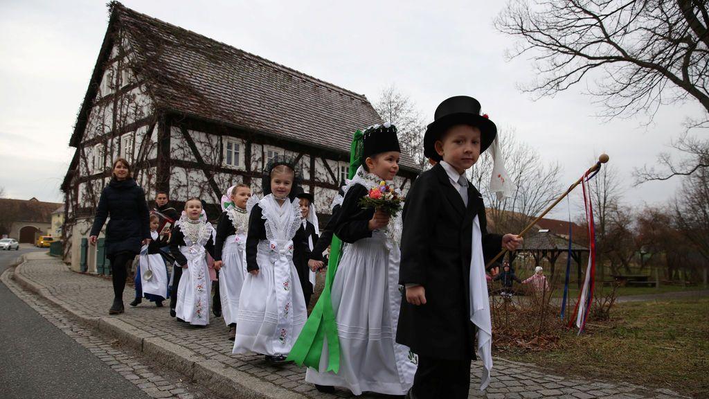 """Niños de la minoría étnica eslava germana visten trajes tradicionales durante un desfile para celebrar el tradicional """"Ptaci Kwas"""" (la unión de los pájaros), un festival celebrado cada 25 de enero, en el que los pájaros agradecen  a los niños que les cuidaran durante el invierno y marca el final de la estación, en Nebelschuetz, al este de Dresden, en Alemania."""