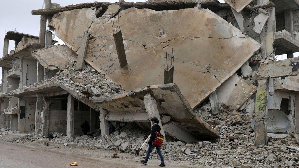 Una estudiante camina delante de un edificio en ruinas a causa de los bombardeos en el area rebelde de la ciudad Deraa, Siria.