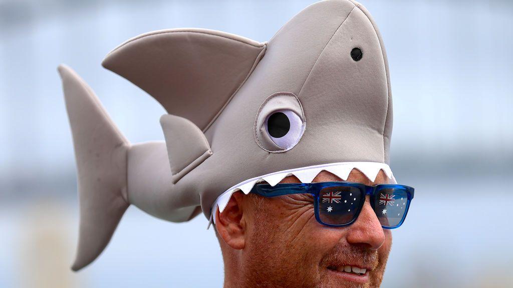 Un hombre lleva un sombrero en forma de tiburón mientras participan en las celebraciones por el Día de Australia