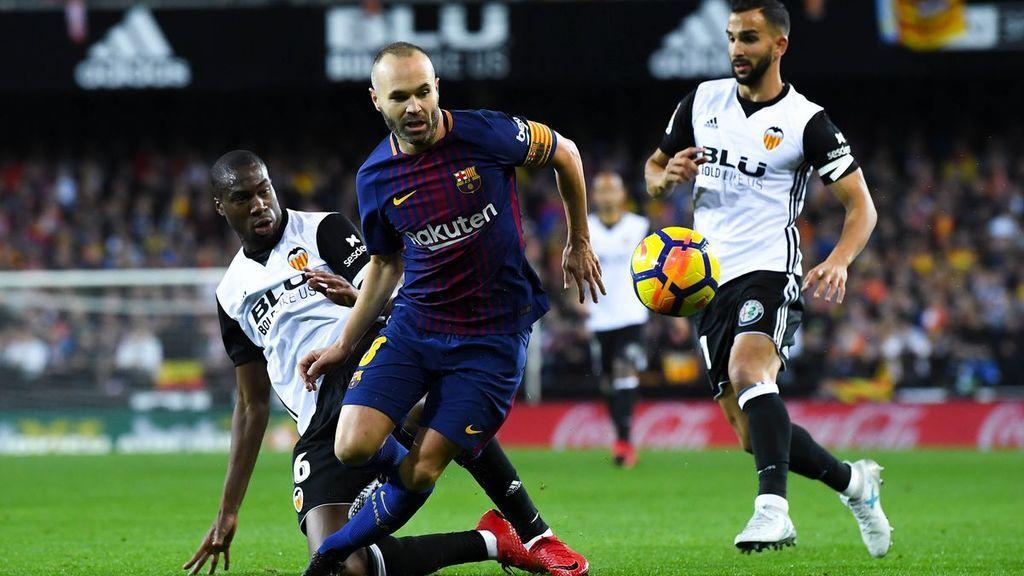 Geoffrey Kondogbia y Andrés Iniesta disputan un balón ante la mirada de Martín Montoya en el encuentro de la primera vuelta de la Liga entre Valencia y F.C. Barcelona.