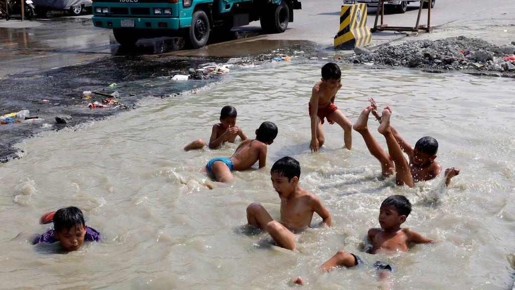 Unos niños nadan en una carretera en reparación en el distrito de Tondo, Filipinas