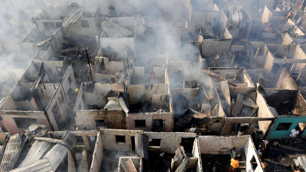 Las víctimas del fuego tamizan a través de las ruinas de sus casas, que fueron destruidas por un incendio en Paranaque, Metro Manila, Filipinas
